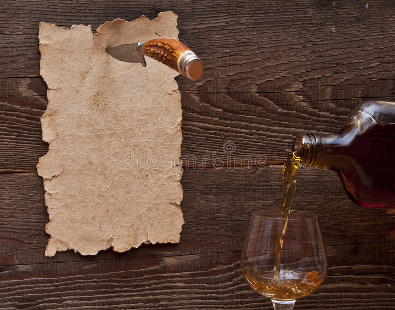 Old paper pinned to a wooden wall with a knife. And the glass with splashes brandy stock photos
