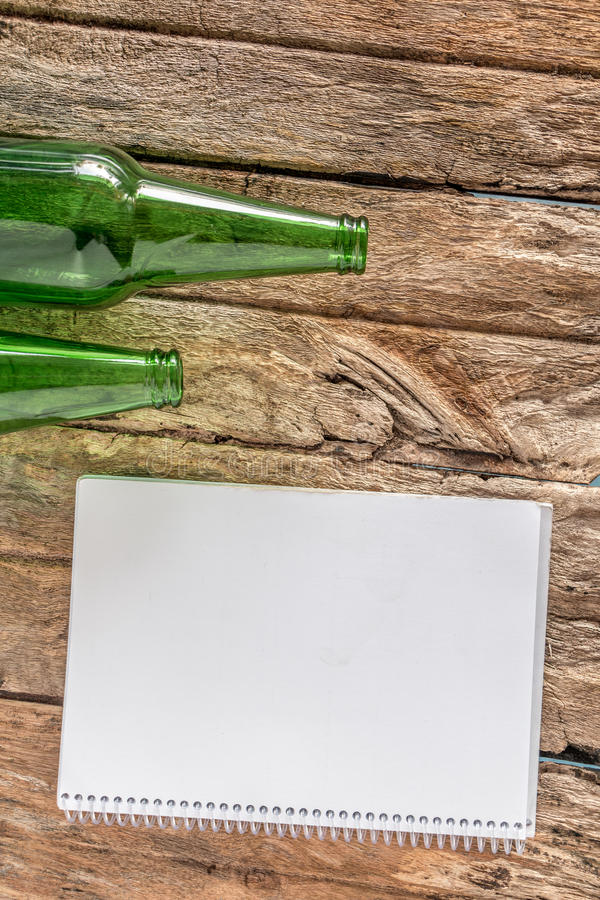 Old paper is placed on the table with a bottle of empty wine pla stock photo