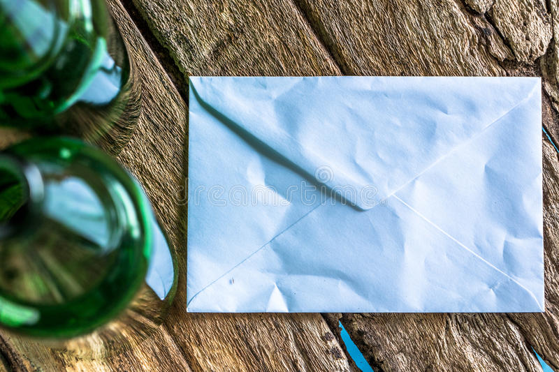 Old paper is placed on the table with a bottle of empty wine pla royalty free stock photography