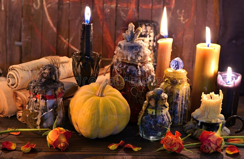 Old paper scrolls, pumpkin, candles and magic bottles on witch table stock image