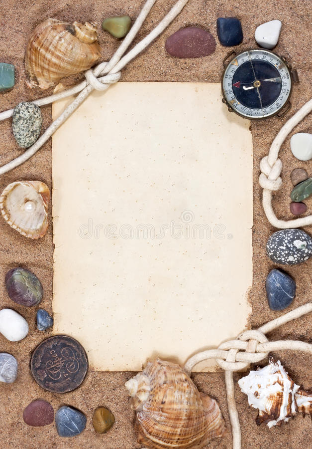 Old paper, sea shells and rope on sand background stock photo