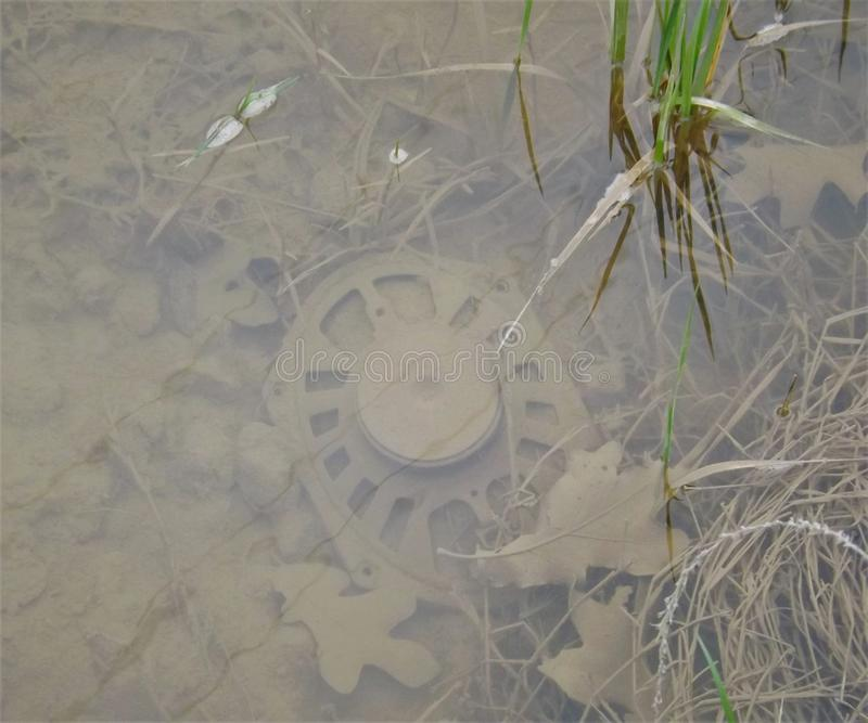 Trash in water beside a road royalty free stock photography