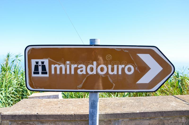 Old, partly damaged brown tourist sign saying miradouro in Portuguese. Information signs. Marking system. Arrow with a symbol of. Binocular. TRANSLATION royalty free stock image