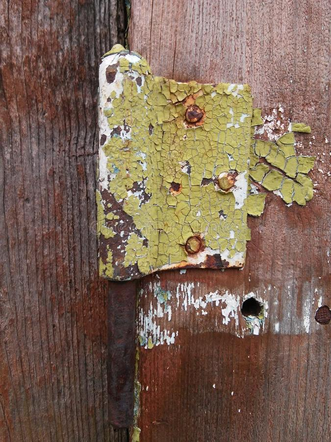 Old parts of old buildings: peeled paints and rusty screws on the hinge of door stock photo