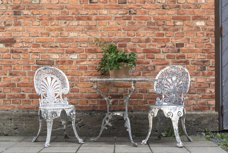 Old, patinated garden furniture against brick wall. Set of old, patinated garden dining chairs and table in front of beautiful brick wall. Old barn/factory door stock photos