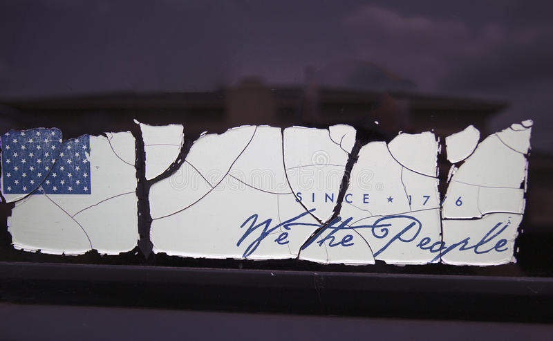 Old patriotic bumper sticker with cracks through it. Mesquite, TX USA May 19, 2017: `We The People bumper sticker; a large crack after the US flag and one stock image