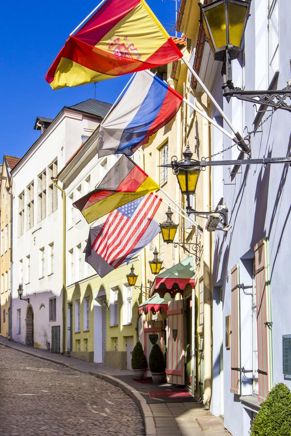 Old paved street with street lights and flags of Germany, USA, Russia and Spain, hanging on colorful houses, Tallinn, Estonia stock photography