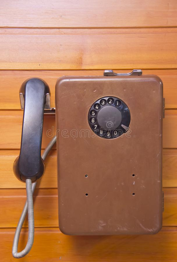 Old pay phone with dial pad on wooden background stock image