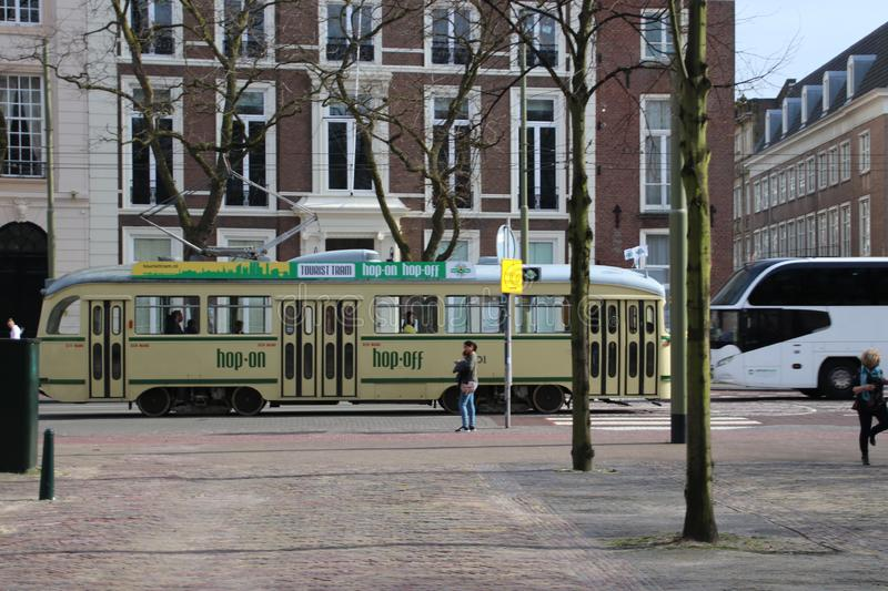 Old PCC tram in yellow color in the streets of Den Haag as tourist guiding line. stock photography