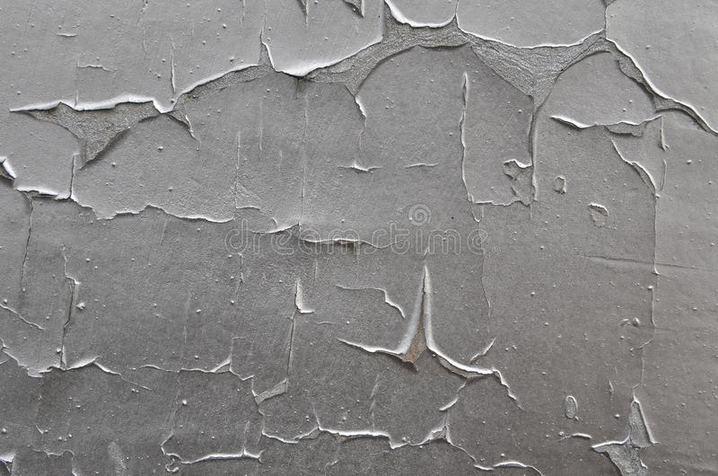 Old peeling silver paint. Weathered peeling cracked silver paint airbrushed on concrete wall stock photos