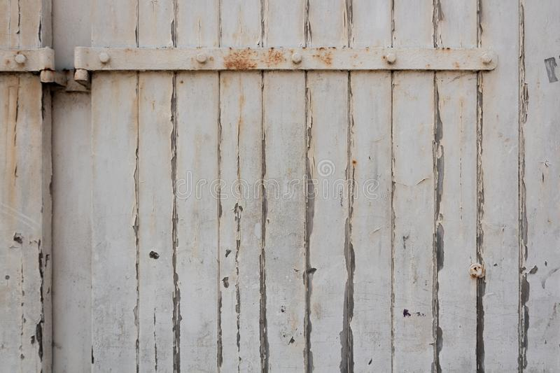 Old, peeling white-painted wall with a rusty door hinge royalty free stock photos
