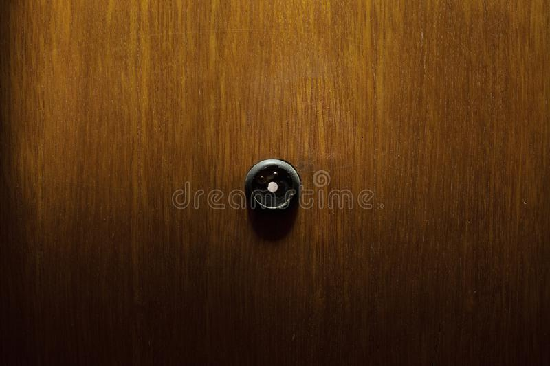 Peephole in wooden doors. Old peephole in wooden doors, abstract composition stock photos