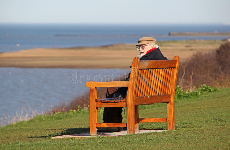 Old pensioner man on coastal bench. Photo of a male pensioner sitting on coastal bench looking out to sea at whitstable in kent.photo taken 9th march 2017 royalty free stock photo