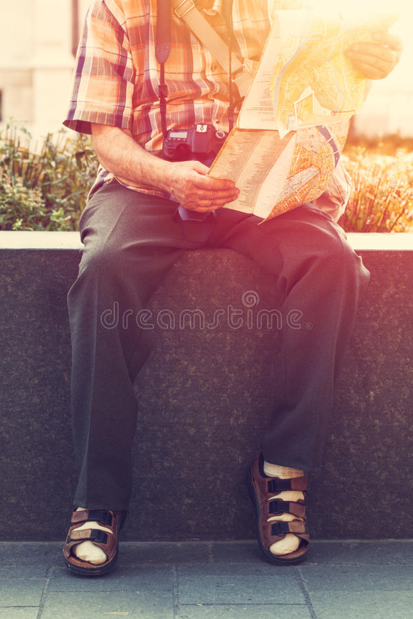 Old pensioner in socks and sandals searching destination on map royalty free stock photography