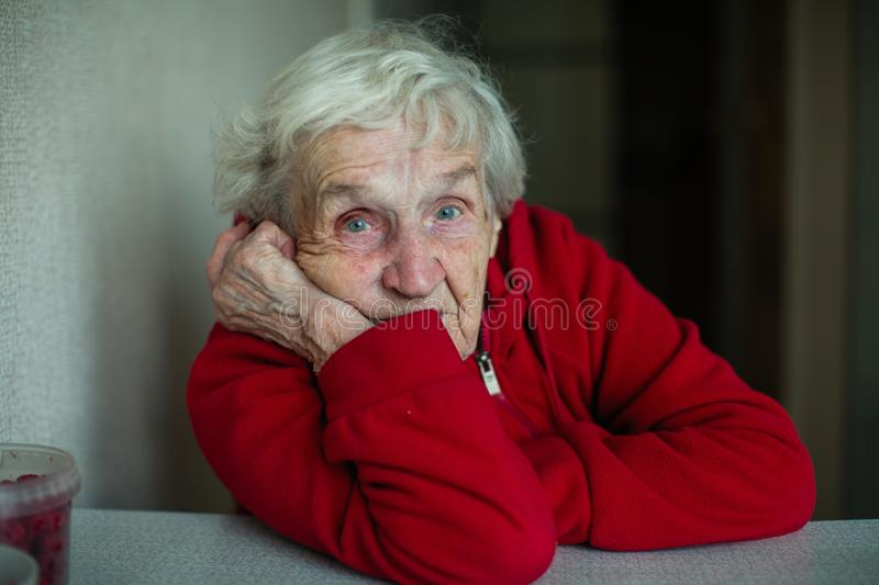 An old pensioner woman in her house, closeup portrait. stock image