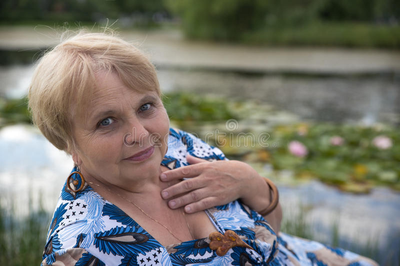 Old pensioner woman near pond at summer park stock photo