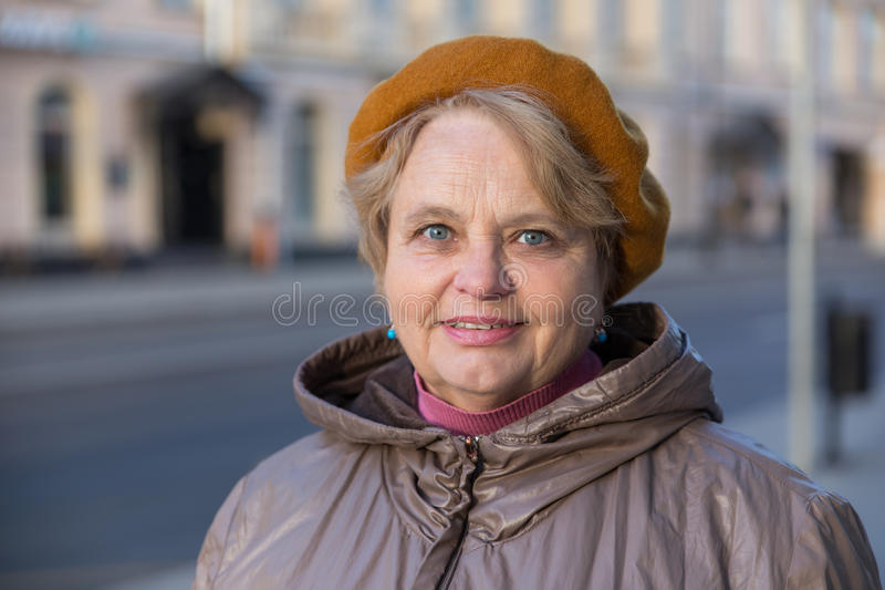 Old pensioner woman walking outside stock photo