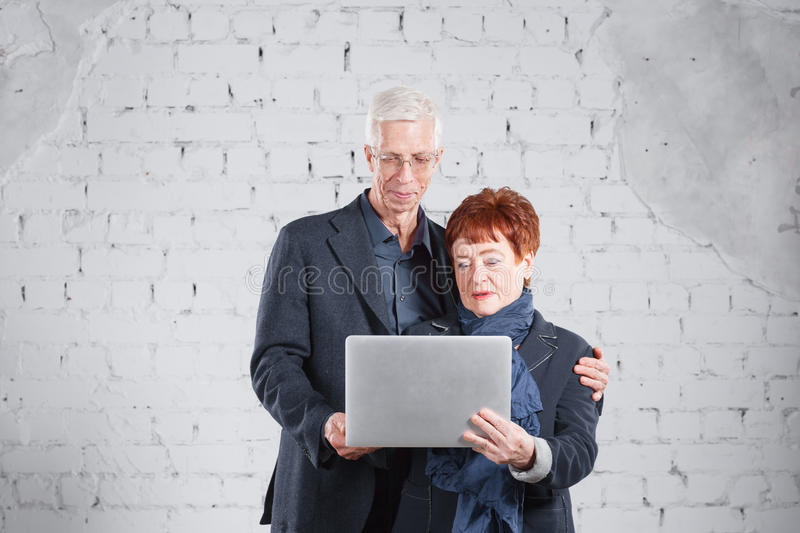Old people hold a laptop and communicate through the Internet. Happy smiling grandpa grandma couple standing cuddling royalty free stock photo