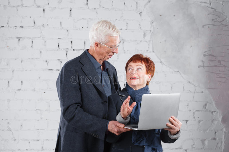 Old people hold a laptop and communicate through the Internet. Happy smiling grandpa grandma couple standing cuddling stock images