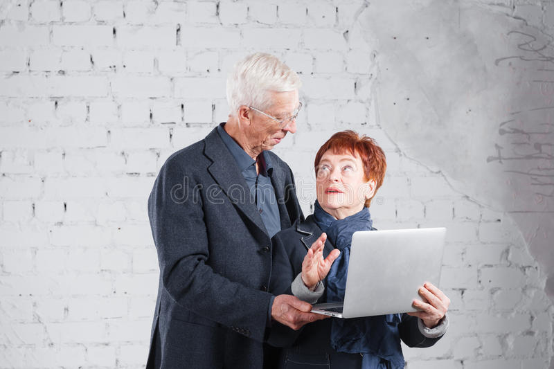 Old people hold a laptop and communicate through the Internet. Happy smiling grandpa grandma couple standing cuddling royalty free stock images