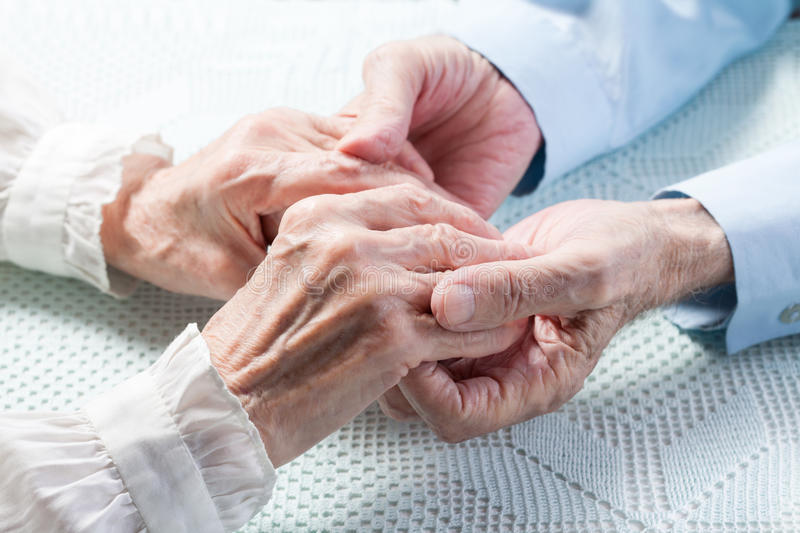 Old people holding hands royalty free stock image