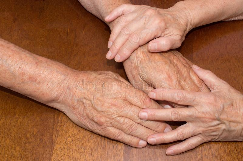 Old people holding hands. Closeup. Old people holding hands. Closeup on wooden table royalty free stock images