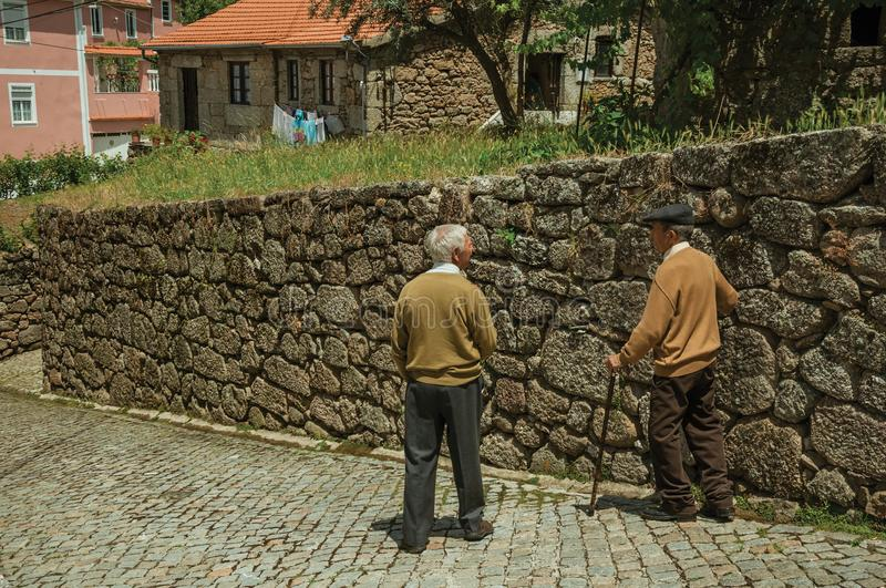 Old people walking down the alley on slope next to stone wall royalty free stock photos