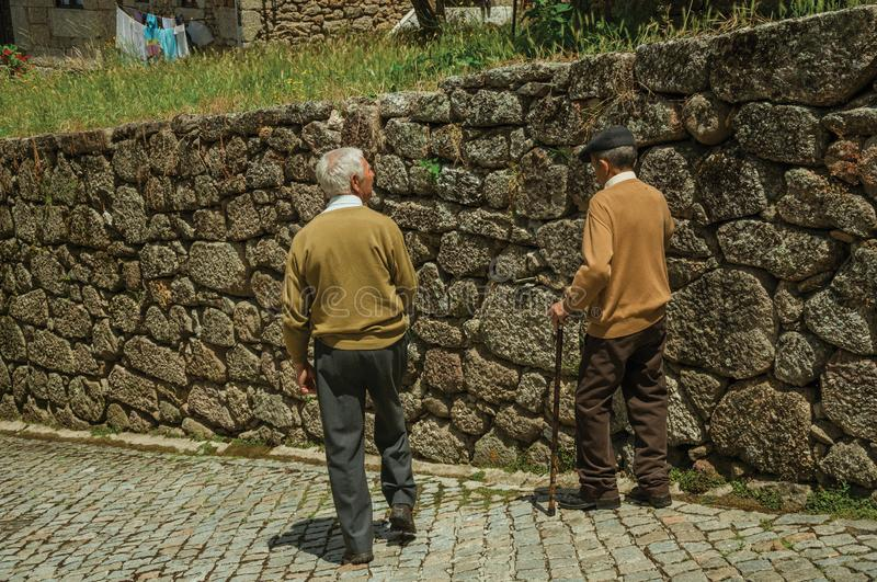Old people walking down the alley on slope next to stone wall royalty free stock images