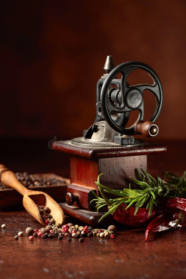 Old pepper mill with cooking utensils,various peppers and rosemary on a brown background stock photo