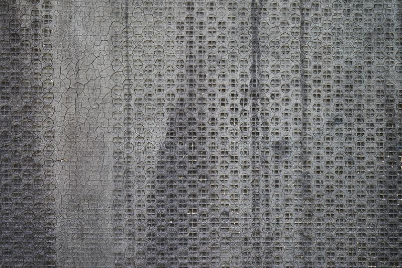 Old perforated metal with grey bituminous coating royalty free stock photography