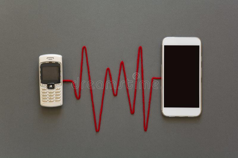 Old phone and new smartphone connected by red pulse laying on grey paper background. Upgrade phone technology royalty free stock photos