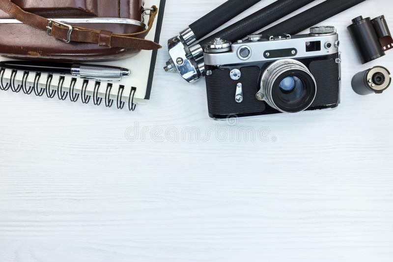 Old photo camera with leather case, tripod, pencil and notebook stock image