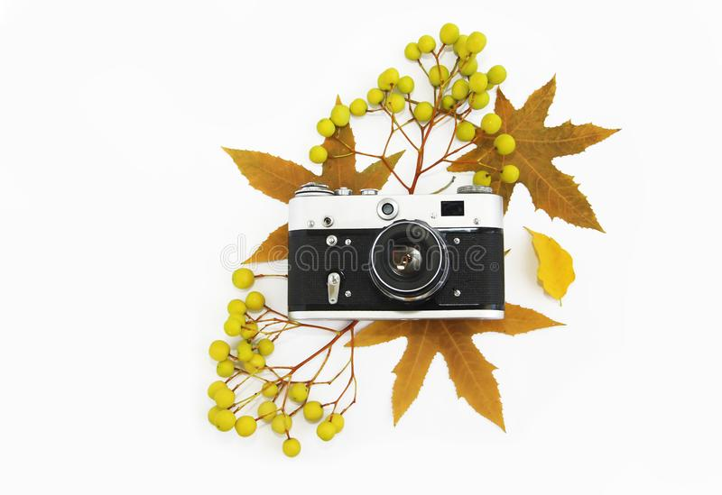 Old photo camera with a lens in a black case on a background of autumn yellow leaves. Old photo camera with a lens in a black case on background of autumn yellow stock image