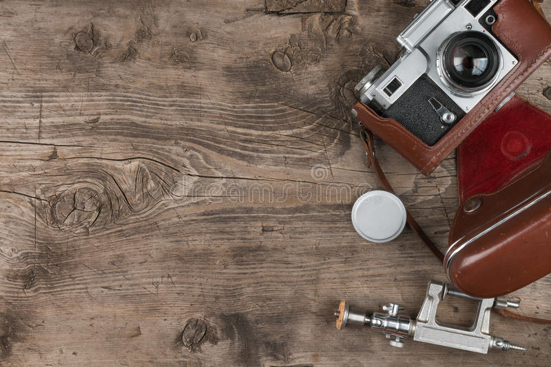 Old photo camera, lens cap, tripod and brown carrying case on wooden background. Copy space. View from above royalty free stock image