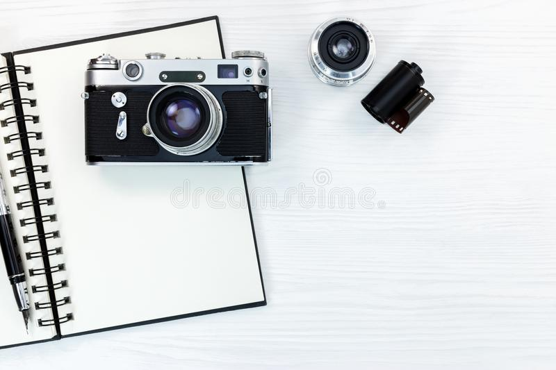 Old photo camera, lens, film roll, notepad and pen on white wood. Old photo camera, lens, film roll, notebook and pen on white wooden background flat view stock photos