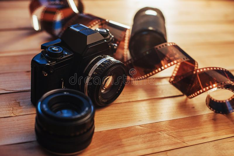 Old photo film and analog camera on table. Roll of photographic . Beautiful vintage design. Old photo film and analog camera on table. Roll of photographic film royalty free stock photos