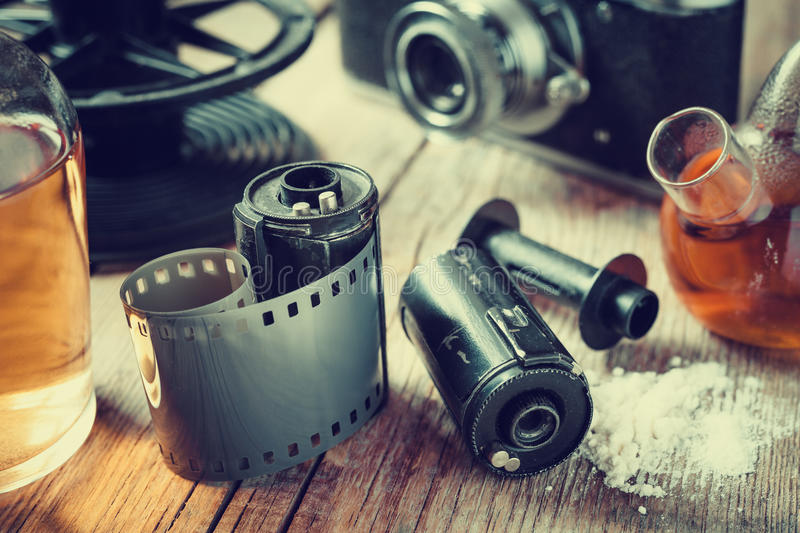 Old photo film rolls, cassette, retro camera and chemical reagents for photographic film. Vintage stylized royalty free stock photos
