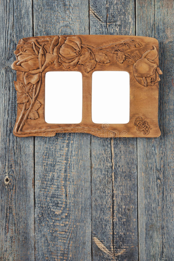 Old photo frame. The old carved frame for photo hanging on a wooden wall royalty free stock photo