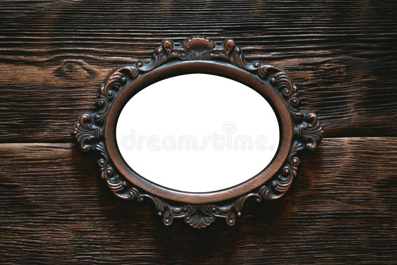 Old photo frame or vintage mirror with a copy space. Vintage photo frame border with a copy space on a wooden wall background royalty free stock images