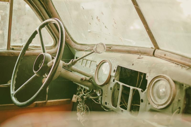 Old photo of Old timer car interior with dusty board and spider web all over the dashboard with rusty levers sepia royalty free stock image