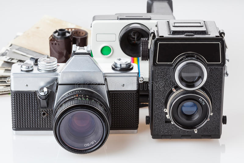 Old photos and cameras. Old black and white photos with cameras in the foreground royalty free stock photo
