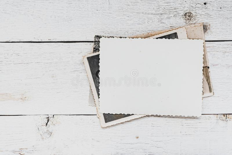 Old photos on white wooden background. Empty photo frame royalty free stock photo