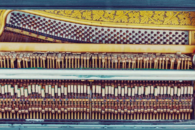 Old piano inside mechanics backgrund and texture. Old piano inside mechanics, colorful hammers and strings background and texture royalty free stock photography
