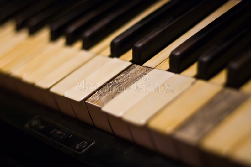 Old Piano keyboard. An old piano keyboard with some broke keys stock image