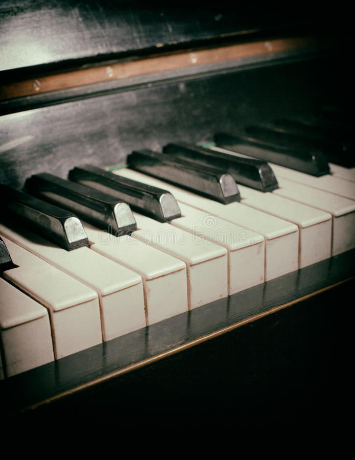 Old piano keyboard. Close up as a music background. With dust and scratches paper texture stock photography