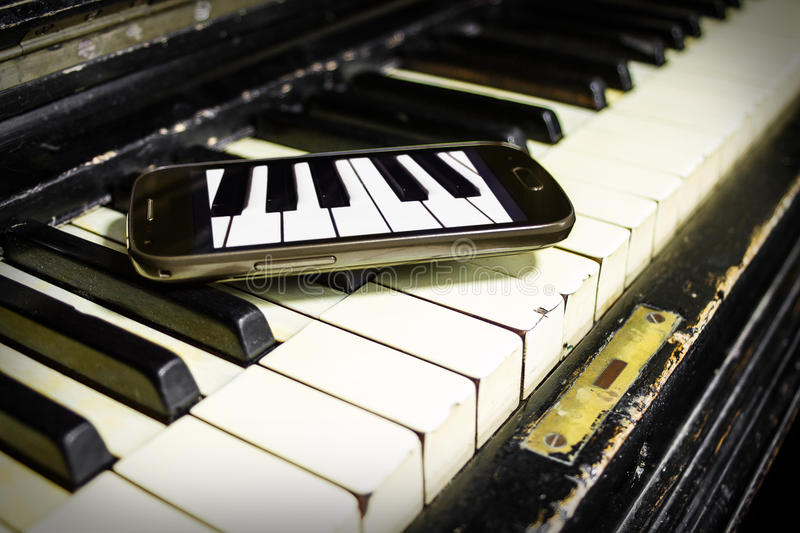 Old Piano and New Keys. Old Piano and smartphone with piano keys image on it stock images