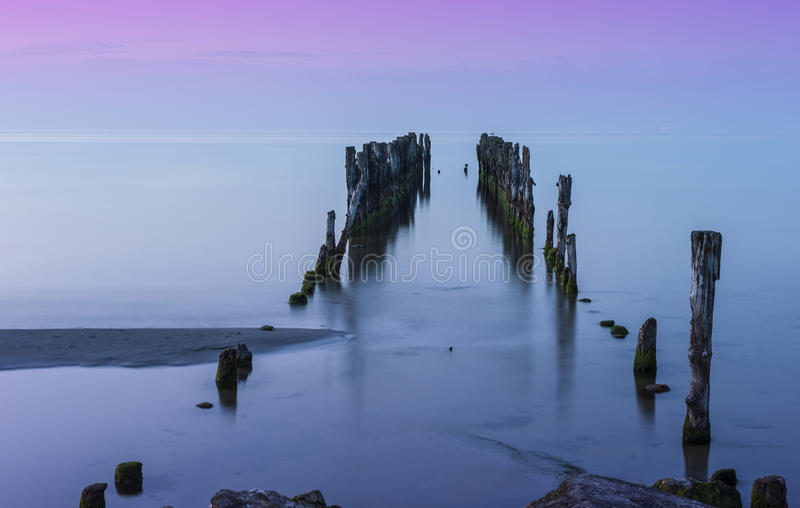 Old pier. Old broken pier at sunset on the coast of the Baltic sea, Latvia stock photography