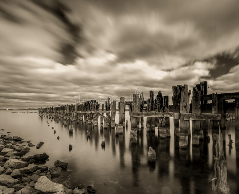 Old Pier. A erie, long exposure shot of the old pier in Prescott, Ontario, Canada with glassy waters, moving clouds royalty free stock images