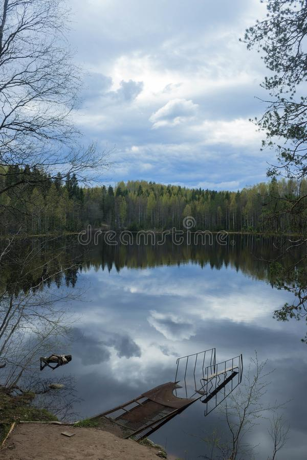 Old pier on a forest lake. Partly cloudy. Silence, peace and mystery royalty free stock image