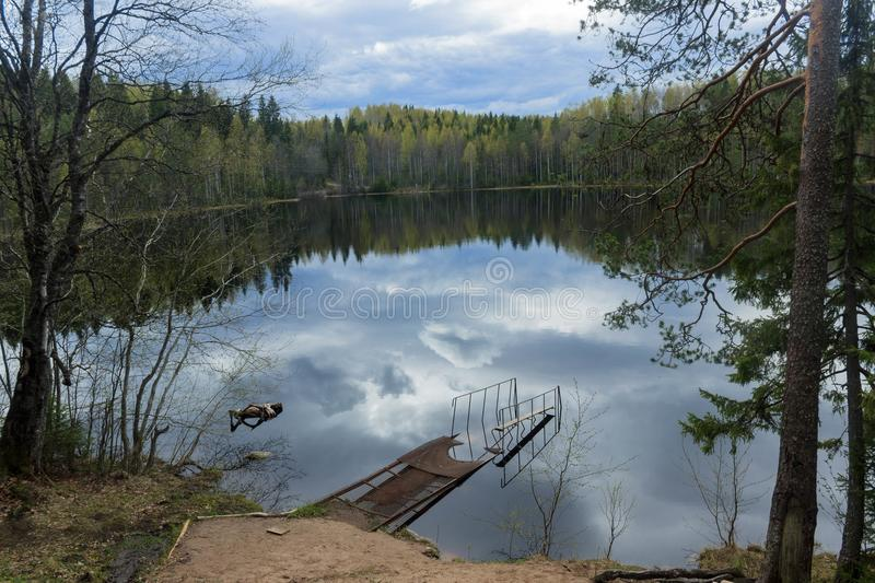 Old pier on a forest lake. Partly cloudy. Silence, peace and mystery stock images